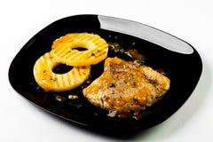 Κρέας και ανανάς στη σχάρα με τη σάλτσα στο μαύρο πιάτο στο άσπρο β Στοκ φωτογραφία με δικαίωμα ελεύθερης χρήσης