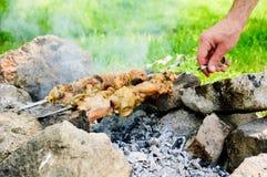 Κρέας κοτόπουλου στα οβελίδια έξω με το χέρι καπνού και μαγείρων - υπαίθρια χειμερινό κόμμα φθινοπώρου Στοκ φωτογραφία με δικαίωμα ελεύθερης χρήσης