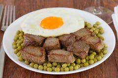 Κρέας με τα μπιζέλια και το τηγανισμένο αυγό στοκ εικόνες