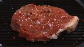 Κρέας μπριζόλας βόειου κρέατος που ψήνεται στη σχάρα σε ένα τηγανίζοντας τηγάνι που ψεκάζεται με τα καρυκεύματα φιλμ μικρού μήκους