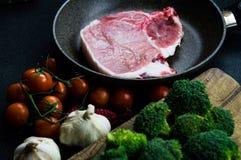 Κρέας σε ένα τηγάνι που μαγειρεύει, ολοκληρωμένος με τις ντομάτες, το μπρόκολο και το σκόρδο Στοκ εικόνα με δικαίωμα ελεύθερης χρήσης