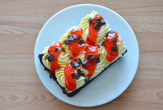 Κρέμα καλύμματος κέικ σοκολάτας και σάλτσα φραουλών σαλτσών στο πιάτο Στοκ Εικόνες