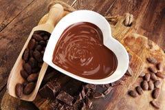 Κρέμα σοκολάτας που λειώνουν και κομμάτια σοκολάτας στον ξύλινο πίνακα Στοκ Εικόνα