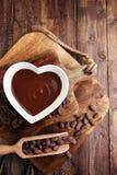 Κρέμα σοκολάτας που λειώνουν και κομμάτια σοκολάτας στον ξύλινο πίνακα Στοκ Φωτογραφία