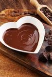 Κρέμα σοκολάτας που λειώνουν και κομμάτια σοκολάτας στον ξύλινο πίνακα Στοκ εικόνες με δικαίωμα ελεύθερης χρήσης