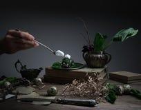 Κρέμα χεριών με ένα κουτάλι, πιάτο του σπανακιού στον πίνακα, παλαιό ασημένιο βάζο Μαύρη ανασκόπηση Στοκ Φωτογραφίες