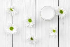 Κρέμα Chamomile Πρόσωπο και προσοχή σωμάτων Καλλυντικά στο μικρό βάζο κοντά στα chamomile λουλούδια στην άσπρη ξύλινη τοπ άποψη υ στοκ εικόνες