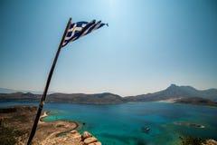 Κρήτη, Ελλάδα: Ελληνική σημαία πέρα από το νησί Gramvousa και τη λιμνοθάλασσα Balos Στοκ φωτογραφία με δικαίωμα ελεύθερης χρήσης