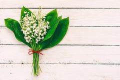 Κρίνοι λουλουδιών της κοιλάδας στο άσπρο ξύλινο υπόβαθρο με το διάστημα αντιγράφων Στοκ φωτογραφία με δικαίωμα ελεύθερης χρήσης