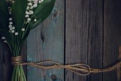 Κρίνος της κοιλάδας στον παλαιό ξύλινο πίνακα στοκ εικόνες με δικαίωμα ελεύθερης χρήσης