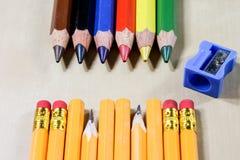 Κραγιόνια και ξύστρα για μολύβια σε έναν ξύλινο πίνακα γραφείων Κραγιόνια W Στοκ Εικόνες
