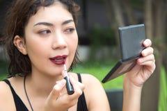 Κραγιόν γυναικείας χρήσης Beautyful για να αποτελέσει το πρόσωπό της με τον καθρέφτη στοκ φωτογραφίες