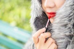 Κραγιόν χρήσης κοριτσιών στο στόμα Καθορισμένο γλυκό προκλητικό κορίτσι μόδας, ασιατικό κραγιόν χρήσης γυναικών στοκ φωτογραφίες