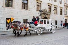 Κρακοβία, Πολωνία - 21 Απριλίου 2017: Άλογα με τις horse-drawn μεταφορές στην παλαιά πόλη στην Κρακοβία Η Κρακοβία είναι η δεύτερ Στοκ φωτογραφία με δικαίωμα ελεύθερης χρήσης