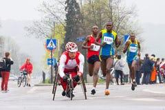 ΚΡΑΚΟΒΙΑ, ΠΟΛΩΝΙΑ - 28 ΑΠΡΙΛΊΟΥ: Δρομείς μαραθωνίου ατόμων Cracovia Marathon.Handicapped σε μια αναπηρική καρέκλα στις οδούς πόλεω στοκ φωτογραφία με δικαίωμα ελεύθερης χρήσης
