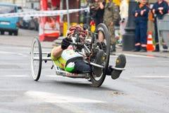 ΚΡΑΚΟΒΙΑ, ΠΟΛΩΝΙΑ - 28 ΑΠΡΙΛΊΟΥ: Δρομείς μαραθωνίου ατόμων Cracovia Marathon.Handicapped σε μια αναπηρική καρέκλα στις οδούς πόλεω στοκ φωτογραφία