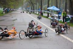ΚΡΑΚΟΒΙΑ, ΠΟΛΩΝΙΑ - 28 ΑΠΡΙΛΊΟΥ: Δρομείς μαραθωνίου ατόμων Cracovia Marathon.Handicapped σε μια αναπηρική καρέκλα στις οδούς πόλεω στοκ εικόνες με δικαίωμα ελεύθερης χρήσης