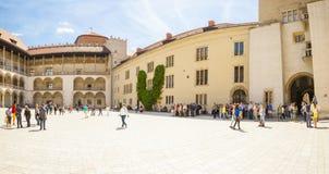 ΚΡΑΚΟΒΙΑ, ΠΟΛΩΝΙΑ - 16 ΜΑΐΟΥ 2015: Τουρίστες που εξετάζουν γύρω το κεντρικό μέρος Wawel το βασιλικό Castle στην Κρακοβία, Πολωνία Στοκ Εικόνες