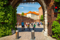 ΚΡΑΚΟΒΙΑ, ΠΟΛΩΝΙΑ - 16 ΜΑΐΟΥ 2015: Τουρίστες που περνούν μέσω της πύλης Bernardine ως κύρια είσοδος ιστορικό σε σύνθετο Wawel το  Στοκ Εικόνες