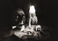 Κρανία και φως κεριών στο μαύρο υπόβαθρο Στοκ Εικόνες