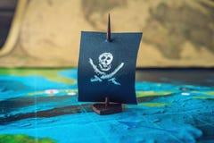Κρανίο και κόκκαλα σημαιών πειρατών βαρκών παιχνιδιών στον παγκόσμιο χάρτη των χειροποίητων επιτραπέζιων παιχνιδιών αγωνιστικών χ Στοκ εικόνα με δικαίωμα ελεύθερης χρήσης