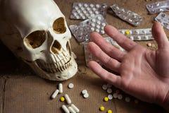 Κρανίο, ταμπλέτες και χέρι ενός νεκρού προσώπου Στοκ Εικόνες