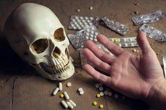 Κρανίο, ταμπλέτες και χέρι ενός νεκρού προσώπου Στοκ εικόνες με δικαίωμα ελεύθερης χρήσης