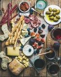 Κρασί και πρόχειρο φαγητό που τίθενται με τα κρασιά, κρέας, ψωμί, ελιές, φρούτα Στοκ Φωτογραφία