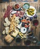 Κρασί και πρόχειρο φαγητό που τίθενται με τα κρασιά, κρέας, ψωμί, ελιές, μούρα Στοκ Εικόνες