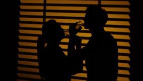 Κρασί κατανάλωσης ζεύγους από την αδελφοσύνη γυαλιών κρασιού σκιαγραφία κλείστε επάνω φιλμ μικρού μήκους
