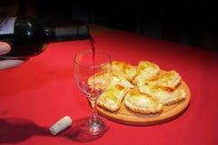 Κρασί που εξυπηρετείται σε ένα γυαλί με τα empanadas Στοκ Φωτογραφία