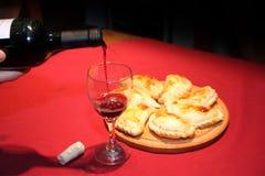 Κρασί που εξυπηρετείται σε ένα γυαλί με τα empanadas Στοκ φωτογραφίες με δικαίωμα ελεύθερης χρήσης