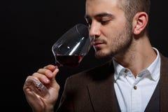 Κρασί ρουθουνίσματος ατόμων σε μια κινηματογράφηση σε πρώτο πλάνο γυαλιού σε ένα μαύρο υπόβαθρο Στοκ Εικόνες