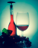 Κρασί σε ένα γυαλί δίπλα σε ένα μπουκάλι του κρασιού και των σταφυλιών σε έναν πίνακα W Στοκ φωτογραφία με δικαίωμα ελεύθερης χρήσης