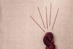 Κρασί-χρωματισμένο νήμα με τις ξύλινες πλέκοντας βελόνες Στοκ Φωτογραφίες