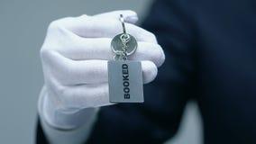 Κρατημένη λέξη στο keychain στο αρσενικό doorman χέρι, υπηρεσία ξενοδοχείων πολυτελείας, έννοια απόθεμα βίντεο