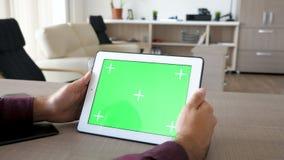 Κρατώντας ένα ψηφιακό PC ταμπλετών στα χέρια με την πράσινη χλεύη χρώματος οθόνης επάνω φιλμ μικρού μήκους