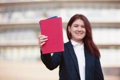 Κρατώντας τα βιβλία πέρα από το ηλιόλουστο υπόβαθρο στοκ φωτογραφία με δικαίωμα ελεύθερης χρήσης