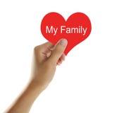 Κρατώντας την κόκκινη καρδιά με το κείμενο η οικογένειά μου Στοκ Εικόνα