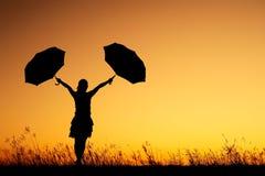 κρατώντας το ηλιοβασίλεμα δύο σκιαγραφιών γυναίκα ομπρελών Στοκ Φωτογραφίες
