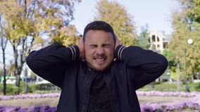 Κραυγάζοντας άτομο που καλύπτει τα αυτιά της με τις ιδιαίτερες προσοχές στο πάρκο απόθεμα βίντεο