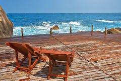 Κρεβάτια ήλιων σε μια ξύλινη γέφυρα στη θάλασσα Στοκ εικόνες με δικαίωμα ελεύθερης χρήσης