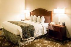 Κρεβάτι βασιλιάδων σε ένα δωμάτιο ξενοδοχείου upscale Στοκ Φωτογραφία