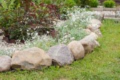 Κρεβάτι λουλουδιών τοπίων που διακοσμείται με την πέτρα και το αμμοχάλικο στοκ φωτογραφία