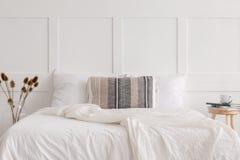Κρεβάτι μεγέθους βασιλιάδων στην άσπρη απλή εσωτερική, πραγματική φωτογραφία κρεβατοκάμαρων στοκ φωτογραφίες με δικαίωμα ελεύθερης χρήσης