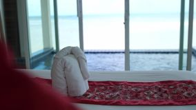 Κρεβάτι ξενοδοχείων στο δωμάτιο ξενοδοχείων πολυτελείας με την άσπρη κλινοστρωμνή στο τζακούζι και τη θάλασσα στο πρώτο πλάνο Ευπ φιλμ μικρού μήκους