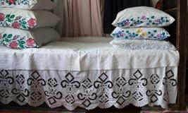 Κρεβάτι που γίνεται με τα κεντημένα φύλλα Στοκ Φωτογραφία