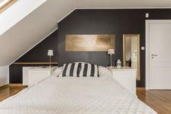 Κρεβάτι στην κρεβατοκάμαρα στη σοφίτα στοκ εικόνα