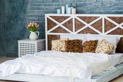 Κρεβατοκάμαρα με το διπλό κρεβάτι, γκρίζος τοίχος τούβλου, ύφος σοφιτών στοκ φωτογραφία με δικαίωμα ελεύθερης χρήσης