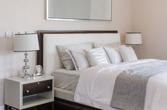 Κρεβατοκάμαρα πολυτέλειας με τον άσπρο κλασικό λαμπτήρα και ρολόι στον πίνακα Στοκ Φωτογραφία
